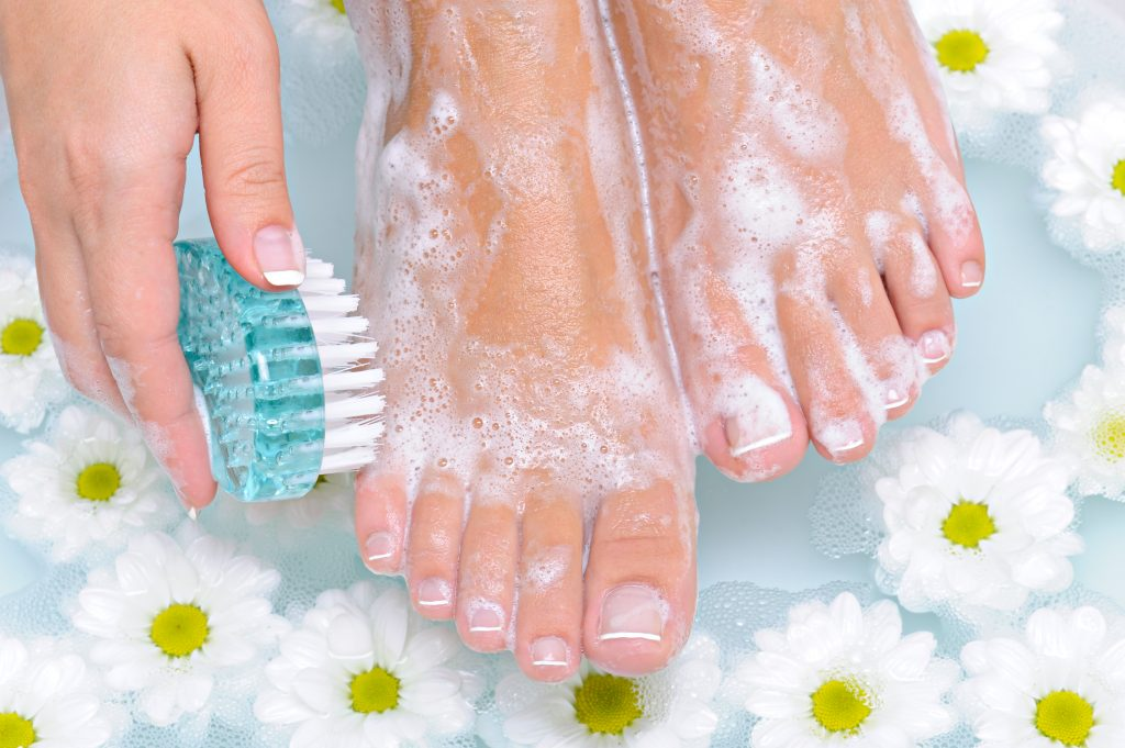 The young woman washes and cleans the beautiful well-groomed legs in water by means of a clearing brush